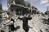 A Palestinian woman reacts at seeing destroyed homes in the northern district of Beit Hanun in the Gaza Strip during an humanitarian truce on July 26...