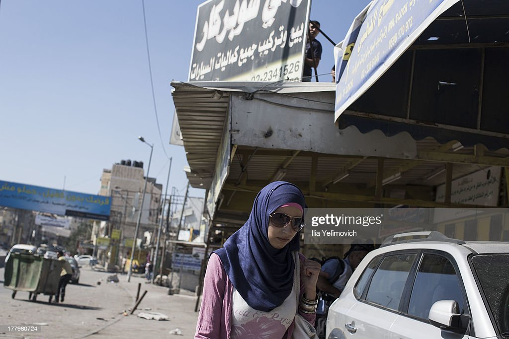 Palestinian woman run for shelter during clashes with Israel Defense Forces after the funeral held for three Palestinians killed during IDF operation at Kalandia refugee camp on August 26, 2013 in Ramallah, West Bank.