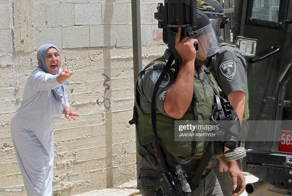 A Palestinian woman shouts at Israeli border guards during clashes following a protest against the expropriation of Palestinian land by Israel on May 31, 2013 in the village of Kfar Qaddum, near the occupied West Bank city of Nablus. AFP PHOTO/JAAFAR ASHTIYEH