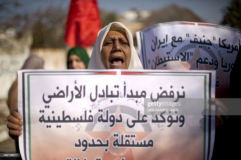 A Palestinian woman shouts slogans holding a placard during a protest of the 'Democratic front for the liberation of Palestine' against renewed peace...