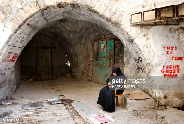 A Palestinian woman sits in the old city of the West Bank city of Hebron on May 8 2017 After half a century of occupation Hebron remains an anomaly...