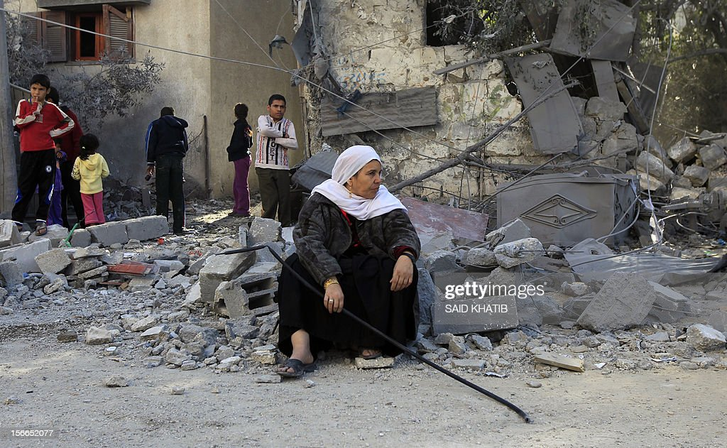 A Palestinian woman sits on the rubble of her destroyed house following Israeli air strikes on the southern Gaza Strip town of Rafah on November 18, 2012. Israeli war planes hit a Gaza City media centre and homes in northern Gaza in the early morning, as the death toll mounted, despite suggestions from Egypt's President Mohamed Morsi that there could be a 'ceasefire soon.' AFP PHOTO/ SAID KHATIB