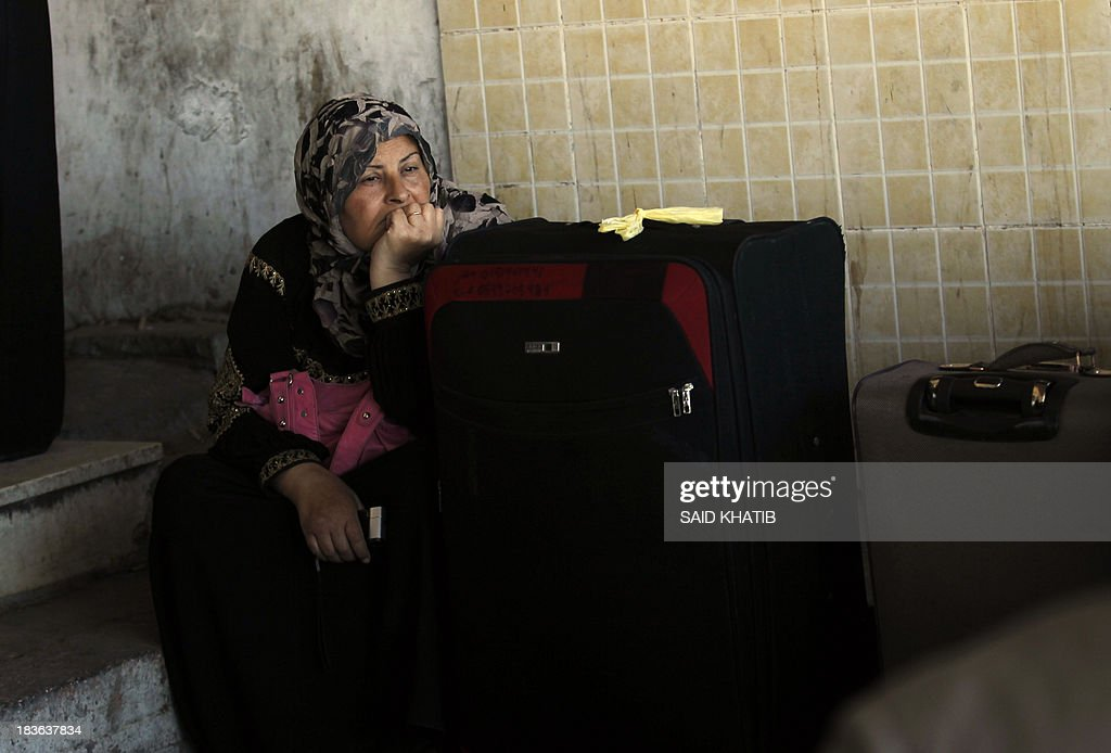 A Palestinian woman sits waiting to cross into Egypt at the Rafah crossing terminal in the southern Gaza Strip on the border with Egypt on October 08, 2013. Hundreds of patients, students and foreign residents from the Palestinian side have rushed to the Rafah crossing after the Egyptian announcement of re-opening it for 5 days.