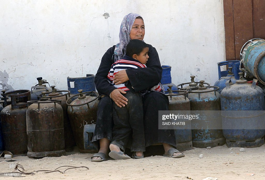 A Palestinian woman sits with her child on empty bottles as she queues to have her cooking gas bottles refilled in Rafah, in the southern Gaza Strip on November 6, 2013. Palestinian officials said Israel has limited the quantity of cooking gas entering into Gaza, which causes a shortage.