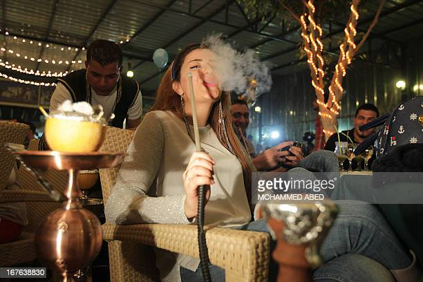 A Palestinian woman smokes water pipe as she watches alongside her husband the performance by Palestinian singer Mohammed Assaf in the Arab Idol...