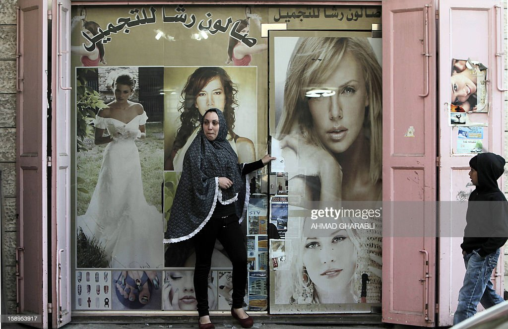 A Palestinian woman stands in front of a hair and beauty parlour as she watches Israeli, Palestinian and foreign activists demonstrate against the Israeli occupation and house demolitions in the Arab east Jerusalem neighbourhood of Issawiya on January 4, 2013.