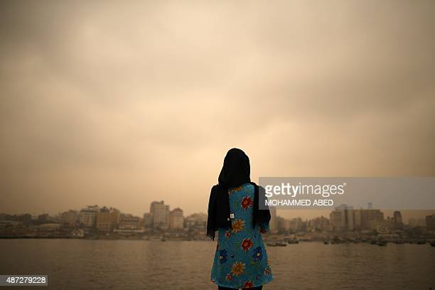 A Palestinian woman stands in front of the sea as a sandstorm blows over the Gaza Strip on September 8 2015 in gaza City A dense sandstorm engulfing...
