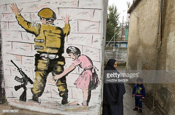 Palestinian woman stands with a child in an alley next to reproduction of a mural by British street artist Banksy originally painted on the wall of...