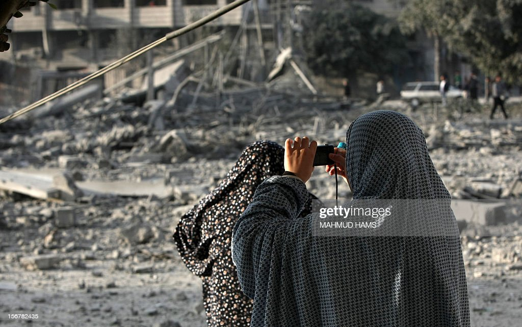 A Palestinian woman takes a picture of the destroyed compound of the internal security ministry in Gaza City after it was targeted by an Israeli air strike overnight on November 21, 2012. Fighting raged on both sides of Gaza's borders Wednesday despite intensified efforts across the region to thrash out a truce to end a week of violence that has cost 136 Palestinian and five Israeli lives. AFP PHOTO/MAHMUD HAMS
