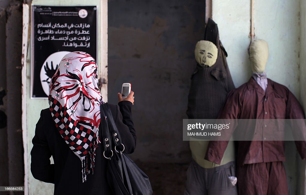 A Palestinian woman takes pictures during a visit of a building which used to be an Israeli prison to keep Palestinians during Israel's occupation of Gaza, on April 14, 2013, as part of a tour organized by Hamas to show the facility that has now turned into a memorial center, in Gaza City. Israel has evacuated its settlements and army posts in the Gaza Strip in 2005.