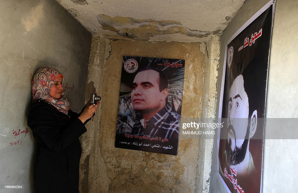 A Palestinian woman takes pictures of posters during a visit of a building which used to be an Israeli prison to keep Palestinians during Israel's occupation of Gaza, on April 14, 2013, as part of a tour organized by Hamas to show the facility that has now turned into a memorial center, in Gaza City. Israel has evacuated its settlements and army posts in the Gaza Strip in 2005.