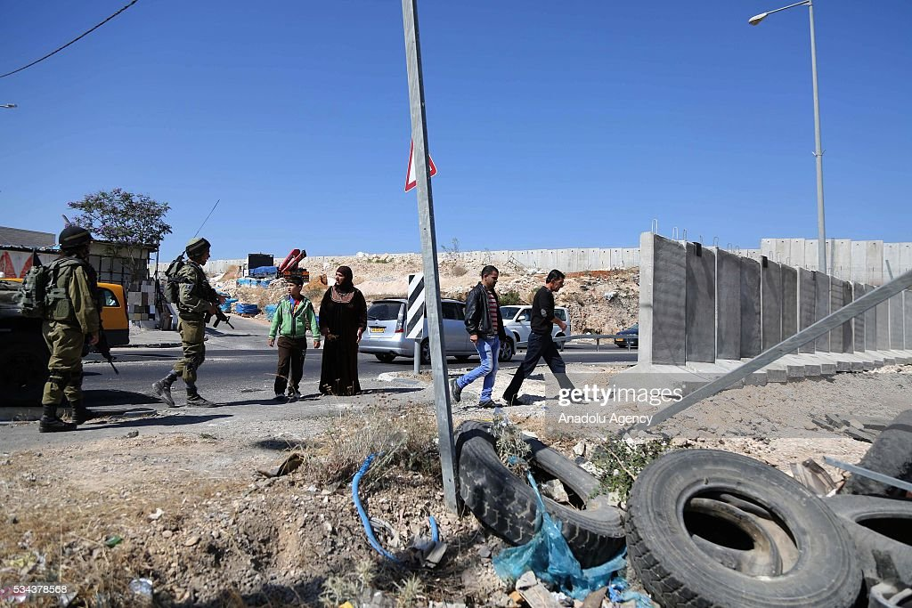 A Palestinian woman talks with Israeli security guard as Israeli security forces increase the security measures around Hizma district of Jerusalem on May 26, 2016.