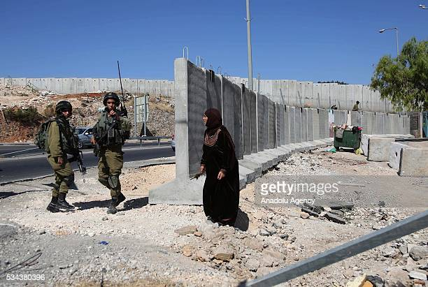 Palestinian woman talks with Israeli security guard as Israeli security forces increase the security measures around Hizma district of Jerusalem on...