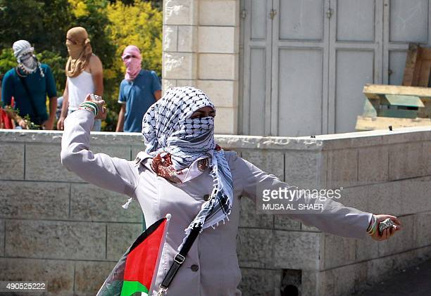A Palestinian woman throws a stone during clashes against Israeli security forces over the AlAqsa mosque compound on September 29 at the main...