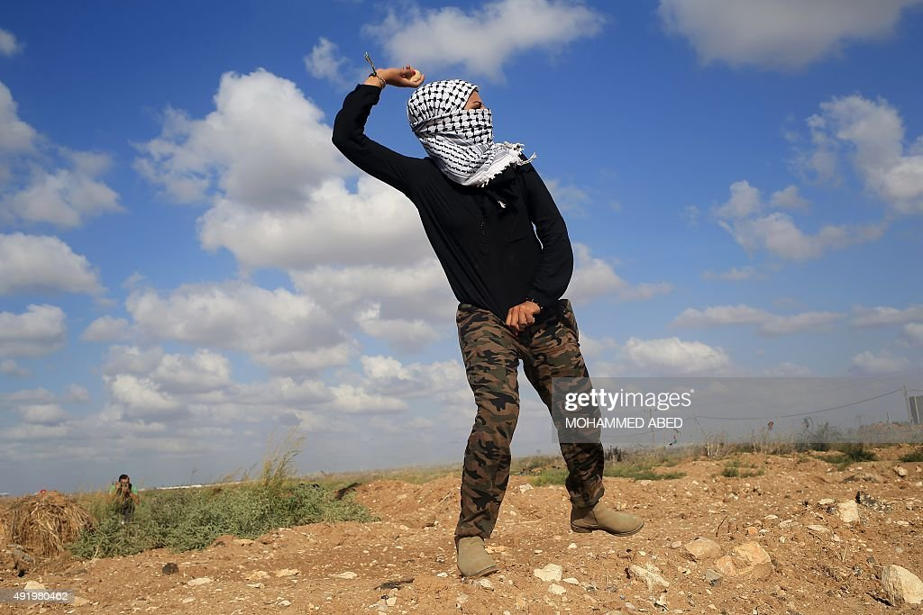 A Palestinian woman throws stones during clashes with Israeli security forces near the border fence between Israel and the Gaza Strip on October 9...