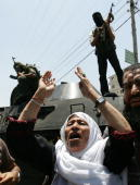Palestinian woman tries with other demonstrators to convince Fatah militants to stop shooting during a clash with militants of the Hamas movement on...