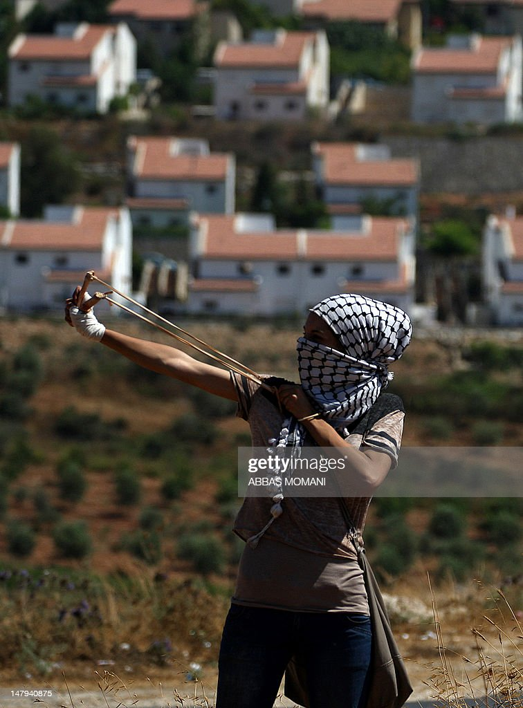 A Palestinian woman uses a slingshot to throw stones towards Israeli troops during a demonstration in the West Bank village of Nabi Saleh to protest against the confiscation of Palestinian land to expand the nearby Jewish settlement of Halamish on July 6, 2012.