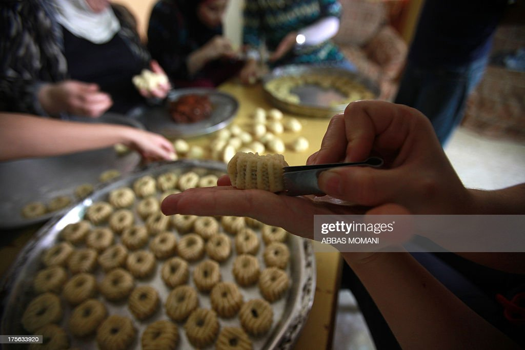 A Palestinian woman uses pincers to decorate traditional biscuits popular on the occasion of Eid al-Fitr at her home in the West Bank city of Ramallah, on August 5, 2013. Muslims around the world are preparing to celebrate the Eid al-Fitr holiday, which marks the end of the fasting month of Ramadan. Preparations include buying new clothes, toys and special sweets.