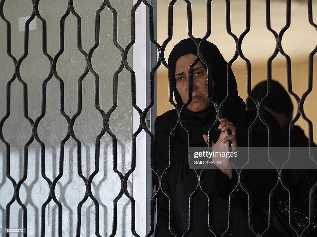 A Palestinian woman waits to cross into Egypt at the Rafah crossing terminal in the southern Gaza Strip on the border with Egypt on October 08, 2013. Hundreds of patients, students and foreign residents from the Palestinian side have rushed to the Rafah crossing after the Egyptian announcement of re-opening it for 5 days.