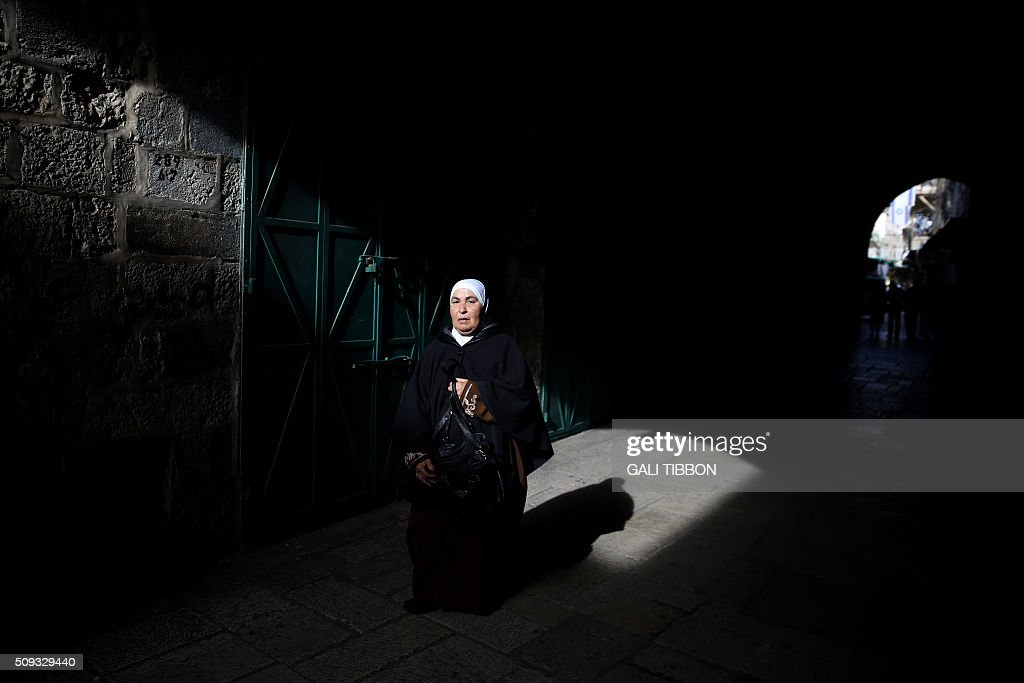 A Palestinian woman walks along an alleyway in the Muslim quarter of Jerusalem's Old City on February 10, 2016. / AFP / GALI TIBBON