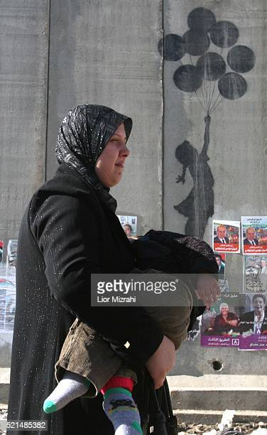 A Palestinian woman walks along Israel's separation wall near the Israeli army's Qalandia checkpoint on Friday January 20 2006 The wall is covered...