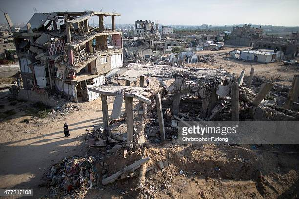Palestinian woman walks among the dust and rubble of bombed homes that still wait to be demolished or rebuilt on June 15 Gaza City Gaza The...