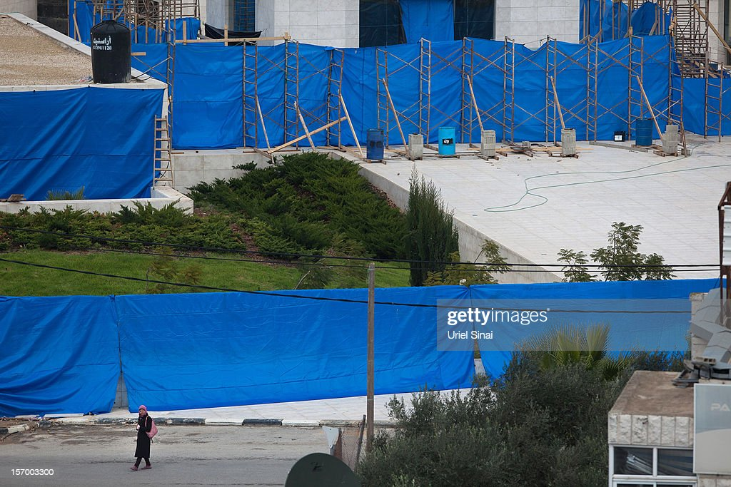 A Palestinian woman walks in front of a cordon of tarpaulin around the mausoleum of the late Palestinian leader Yasser Arafat, on November 27, 2012 in Ramallah, West Bank. A team of investigators last night exhumed and reburied the body of former Palestinian leader Yasser Arafat in a bid to determine whether he was murdered by radiation poisoning. The new probe comes after traces of the deadly radioactive isotope, Polonium-210, were found on his clothing. Arafat died of unexplained causes in a French hospital in November 2004.