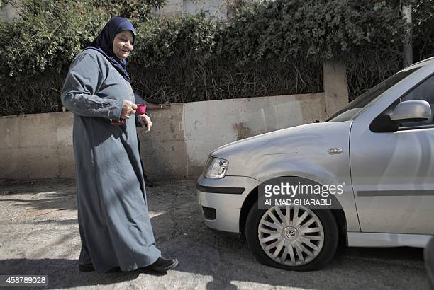 A Palestinian woman walks next to a car whose tyres were slashed in the Arab neighborhood of Beit Safafa in southern Jerusalem on November 11 after...