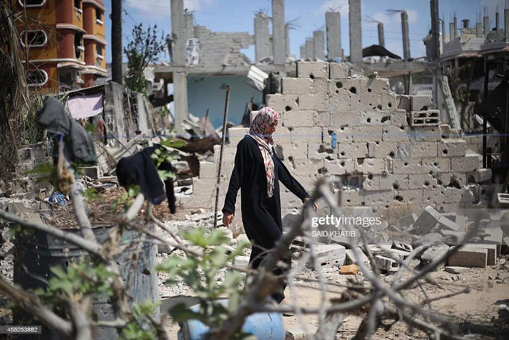 A Palestinian woman walks past a destroyed house in Khan Yunis in the southern Gaza Strip on September 11 2014 Israel's deputy foreign ministerTzahi...