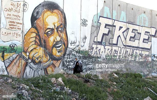 A Palestinian woman walks past a graffiticovered section of the controversial Israeli separation wall showing jailed Fatah leader Marwan Barghuti at...