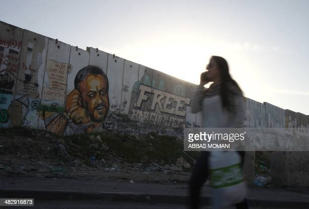 A Palestinian woman walks past a graffiticovered section of the controversial Israeli separation wall showing jailed Fatah movement leader Marwan...