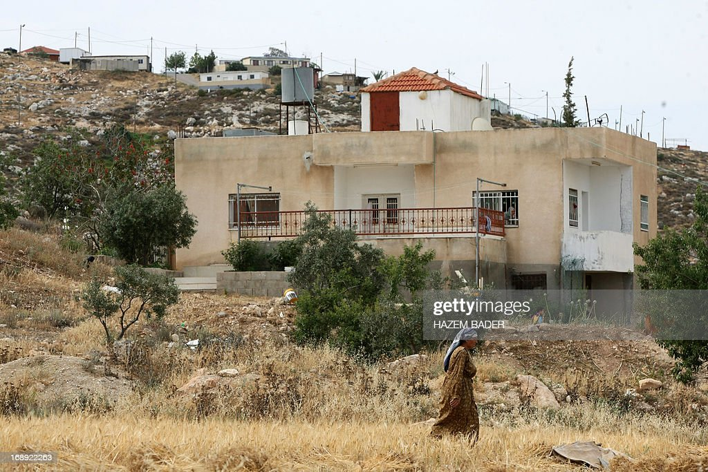 A Palestinian woman walks past a house belonging to a Palestinian family on May 17, 2013 in front of houses in the Mitzpe Lachish Israeli settlement outpost (background) in the West Bank village of Beit Awwa. Israeli settlement watchdog Peace Now said on May 16, 2013 that the government wants to give retroactive approval to four West Bank settlement outposts it had previously pledged to at least partially demolish. Givat Assaf, Givat HaRoeh, Maaleh Rehavam and Mitzpe Lachish outposts are among six listed in a 2005 government report as deserving immediate eviction and later ordered shut by a court order.