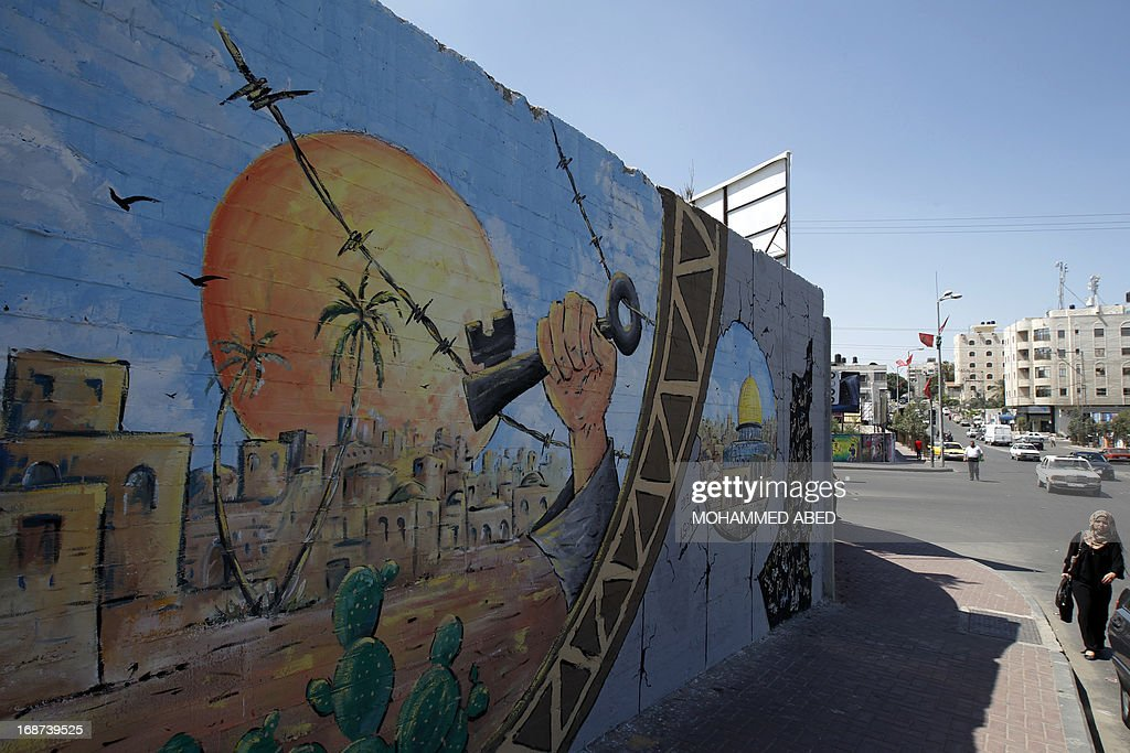 A Palestinian woman walks past a mural marking Nakba in Gaza City, on May 14, 2013 as Palestinians start to mark Nakba, or catastrophe in Arabic, which commemorates the exodus of hundreds of thousands of Palestinians after the establishment of Israel state in 1948. AFP PHOTO/MOHAMMED ABED