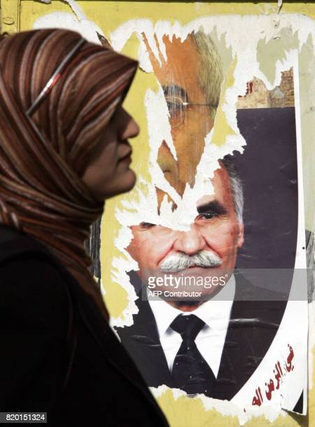 A Palestinian woman walks past an election poster showing a local candidate in East Jerusalem 24 January 2006 a day prior to the Palestinian...