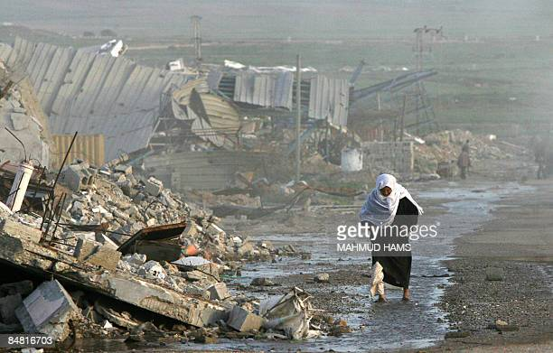 A Palestinian woman walks past buildings destroyed during Israel's 22day offensive in Jabalia in the northern Gaza Strip on February 15 2009 The...