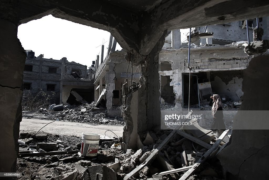 A Palestinian woman walks past destroyed buildings in the northern Gaza Strip city of Beit Hanun on August 22, 2014. The Hamas armed wing declared the truce efforts over after Israel carried out an abortive assassination attempt the previous day on its leader Mohammed Deif, killing his wife and two of his children.