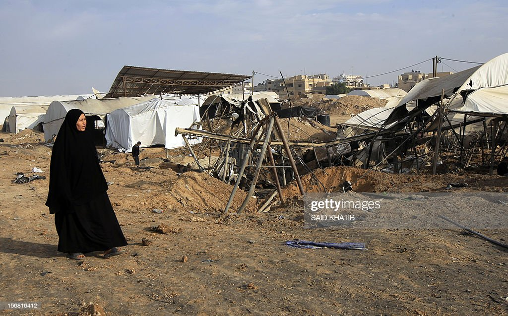 A Palestinian woman walks past destroyed tents near bombed smuggling tunnels between the southern Gaza Strip and Egypt in the border town of Rafah on November 22, 2012. A ceasefire took hold in and around Gaza after a week of cross-border violence between Israel and Palestinian militants that killed at least 160 people.