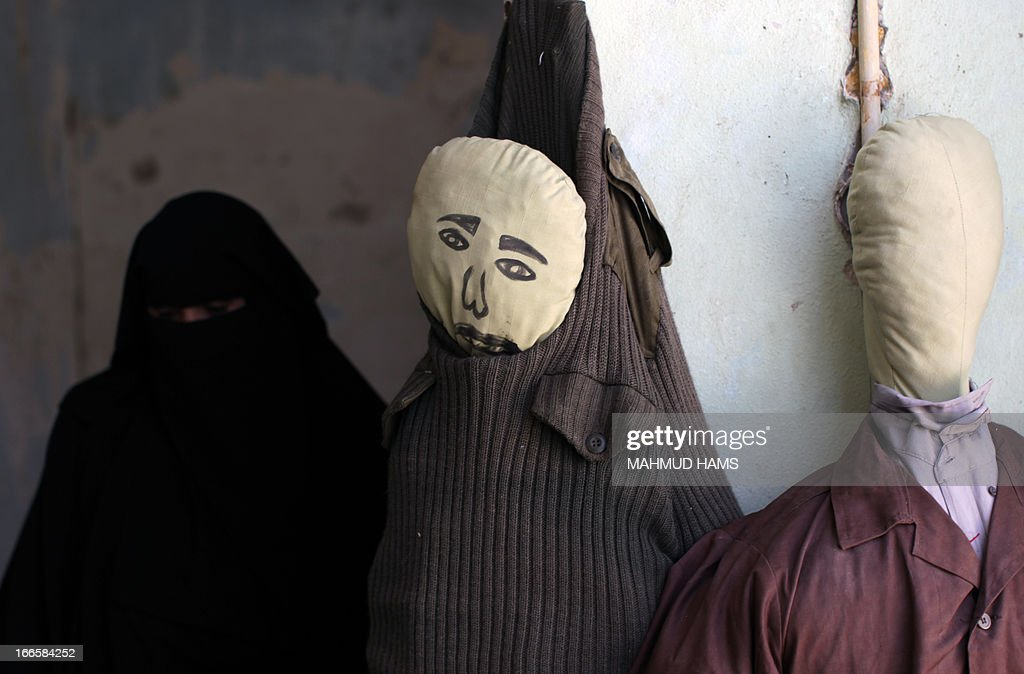 A Palestinian woman (L) walks past dummies during a visit of a building which used to be an Israeli prison to keep Palestinians during Israel's occupation of Gaza, on April 14, 2013, as part of a tour organized by Hamas to show the facility that has now turned into a memorial center, in Gaza City. Israel has evacuated its settlements and army posts in the Gaza Strip in 2005.