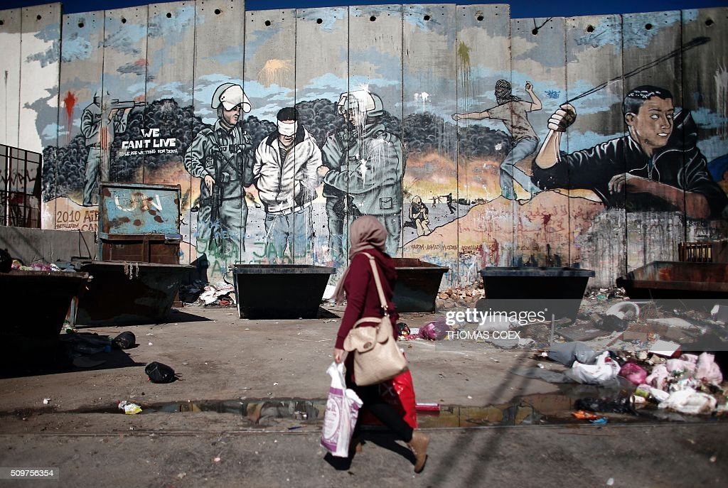 A Palestinian woman walks past graffiti painted on Israel's controversial separation barrier in the Aida refugee camp situated inside the West Bank town of Bethlehem, on February 12, 2016. / AFP / THOMAS COEX
