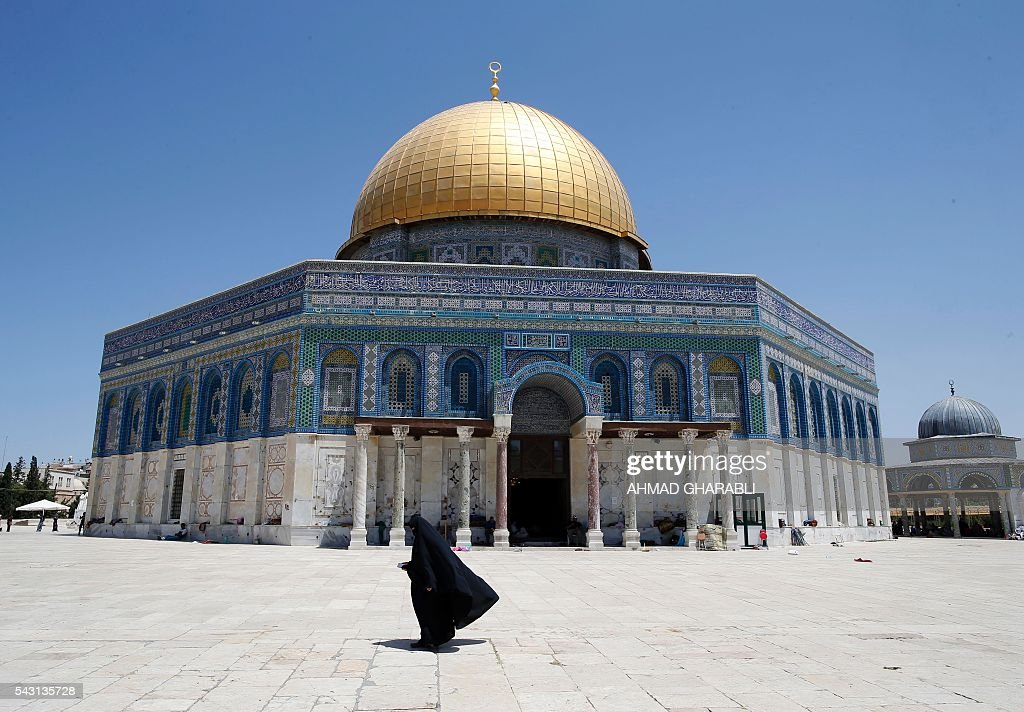 A Palestinian woman walks past the Dome of the Rock in Al-Aqsa Mosque compound in Jerusalem's Old City after clashes erupted at the site between Palestinians and Israeli police on June 26, 2016 during the holy month of Ramadan. Israeli police at Jerusalem's Al-Aqsa mosque compound clashed with Muslims protesting Jewish visits there as the Islamic holy month of Ramadan approached its climax, Palestinians said. / AFP / AHMAD