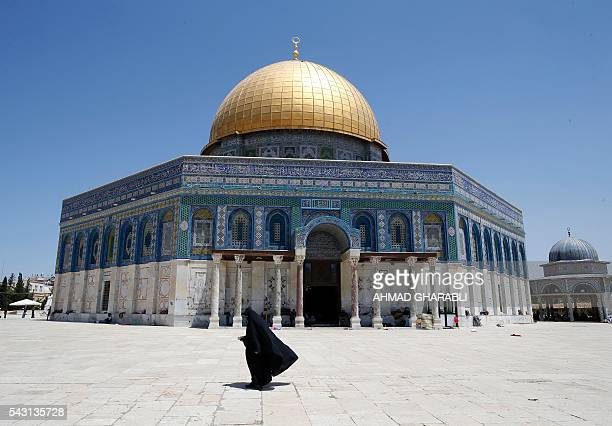 Palestinian woman walks past the Dome of the Rock in AlAqsa Mosque compound in Jerusalem's Old City after clashes erupted at the site between...