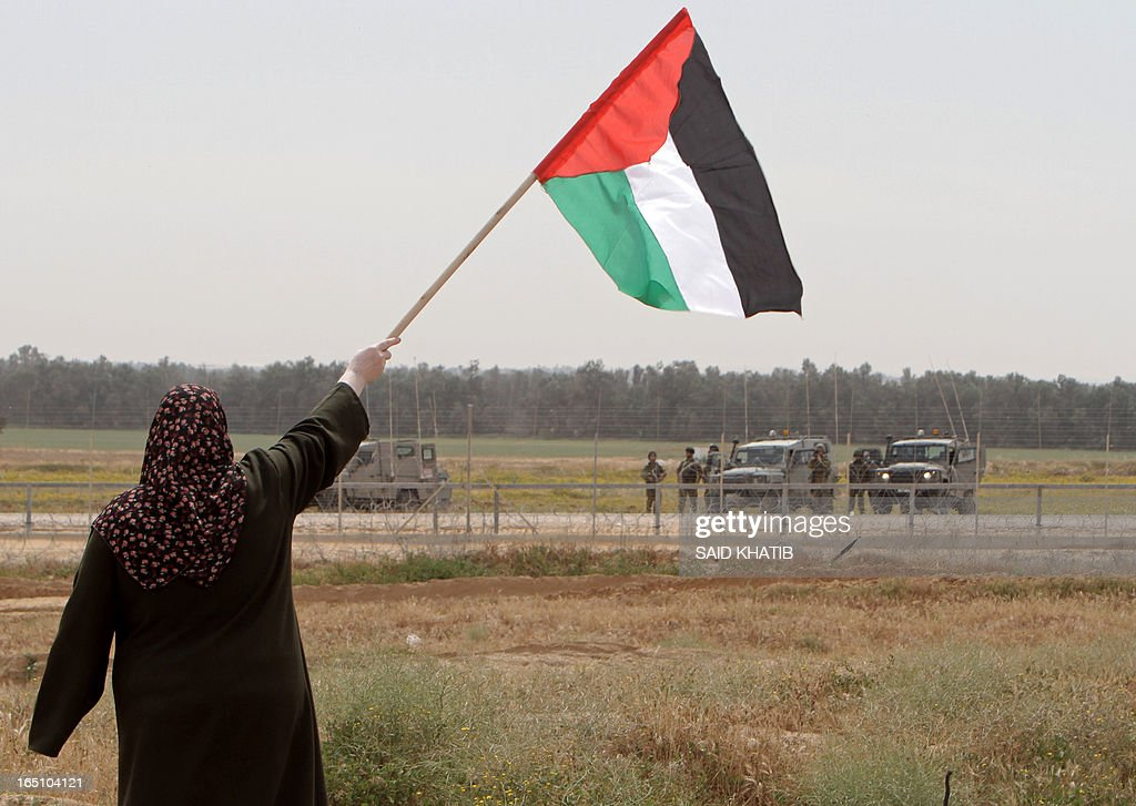 A Palestinian woman waves her national flag opposite Israeli troops taking position on the Israeli side of the border as Palestinians mark Land Day near the southern Gaza Strip's border with Israel, east of Rafah, on March 30, 2013. Land Day commemorates the death of six Arab Israeli protesters at the hands of Israeli troops during mass protests in 1976 against plans to confiscate land in Galilee.