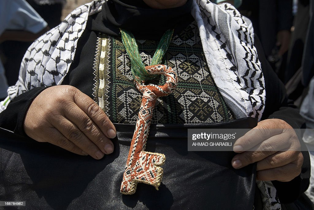 A Palestinian woman wears a key around her neck symbolizing the homes people lost in 1948 when the Jewish state of Israel was created, as she attends a rally outside Damascus gate in Jerusalem on May 15, 2013 to mark the 65th Nakba or 'catastrophe' of the Jewish state's creation in 1948, during which 760,000 Palestinians fled their homes. Thousands of Palestinians took to the streets in the West Bank and the Gaza Strip to demonstrate on Nakba Day and assert their 'right to return' to where their ancestors fled after the Israeli victory over Arab armies.