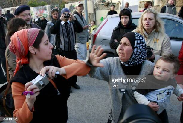 A Palestinian woman who was evicted from her house by Israeli settlers scuffles with a Jewish settler who was trying to take a photograph in front of...