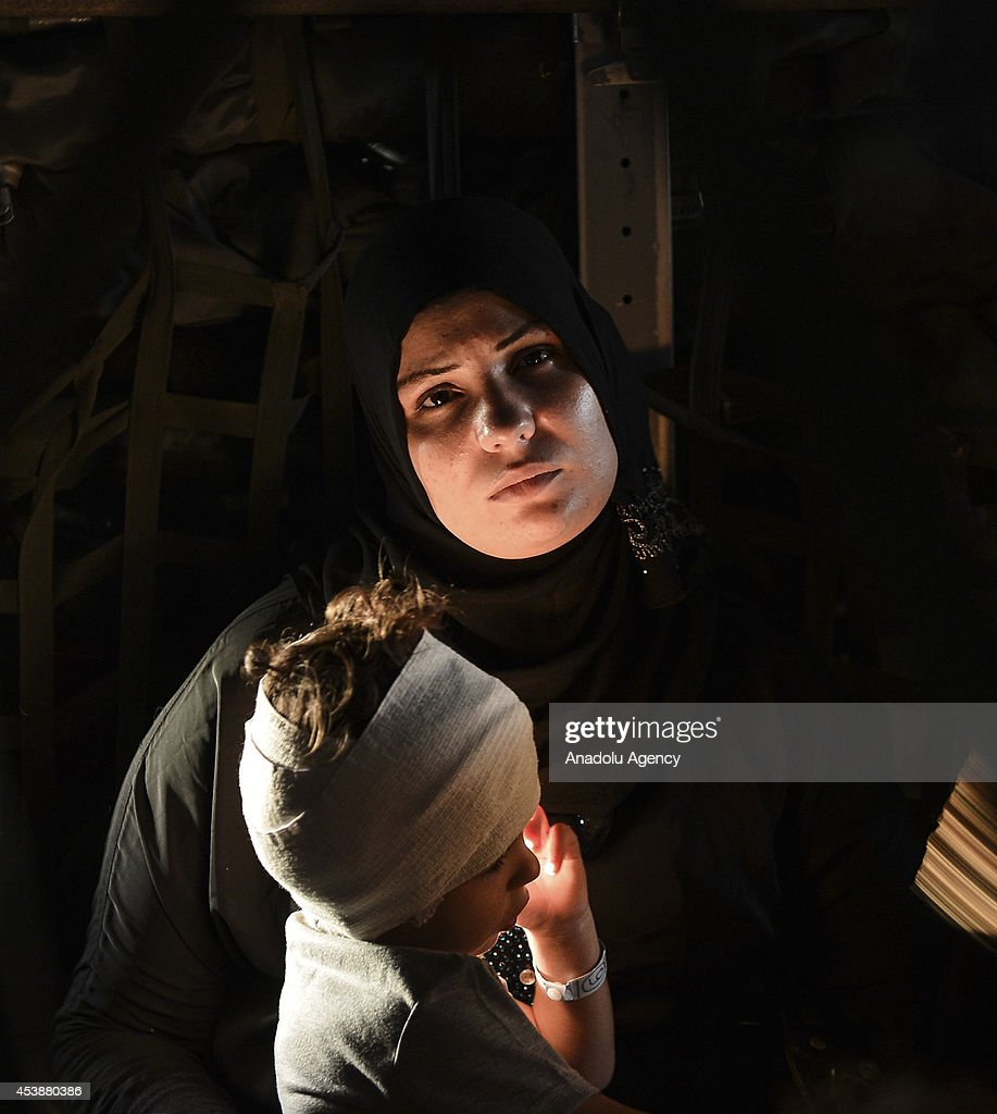 A Palestinian woman with her injured little kid waits at the airport in Istanbul after the aircraft of Turkish air forces carrying 23 injured Palestinians landed on August 20, 2014.