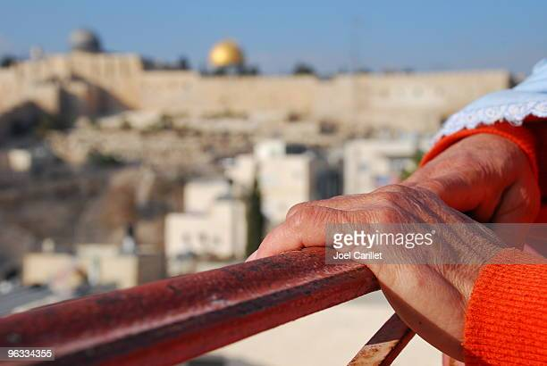 Woman's hands on railing overlooking Jerusalem's Old City