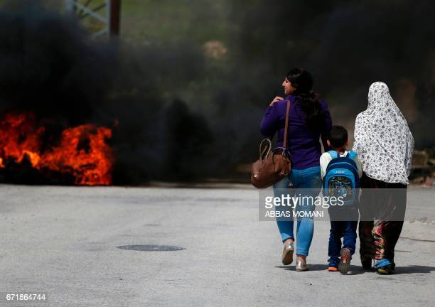 Palestinian women and a school boy walk past burning tyres during clashes between demonstrators and Israeli security forces following a protest in...