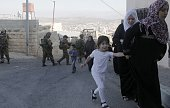 Palestinian women and children walk past Israeli soldiers in a street of the West Bank village of Qabalan during an operation by the Iraeli army...