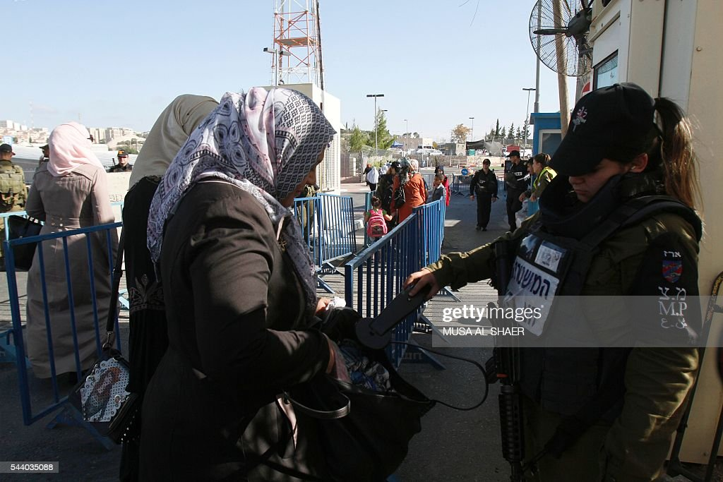 Palestinian women are checked by an Israeli border guard as they cross an Israeli checkpoint between the West Bank town of Bethlehem and Jerusalem, heading to Jerusalem's Al-Aqsa Mosque compound on the forth and last Friday of the Muslim holy month of Ramadan on July 1 , 2016. Israeli authorities announced on June 28 they were closing Jerusalem's flashpoint Al-Aqsa mosque compound to non-Muslim visitors until the end of the Muslim holy month of Ramadan after a series of clashes between worshippers and Israeli police. Clashes have been taking place every morning since the beginning of the week over Jewish visits to the site, with youths throwing stones and security forces firing tear gas and sponge-tipped bullets. / AFP / MUSA