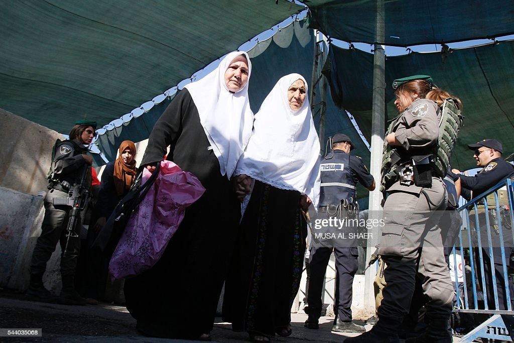 Palestinian women are checked by Israeli border guards as they cross an Israeli checkpoint between the West Bank town of Bethlehem and Jerusalem, heading to Jerusalem's Al-Aqsa Mosque compound on the forth and last Friday of the Muslim holy month of Ramadan on July 1 , 2016. Israeli authorities announced on June 28 they were closing Jerusalem's flashpoint Al-Aqsa mosque compound to non-Muslim visitors until the end of the Muslim holy month of Ramadan after a series of clashes between worshippers and Israeli police. Clashes have been taking place every morning since the beginning of the week over Jewish visits to the site, with youths throwing stones and security forces firing tear gas and sponge-tipped bullets. / AFP / MUSA